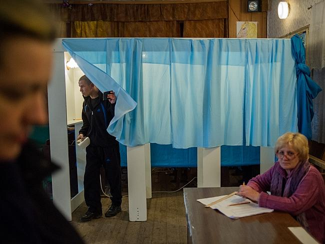The curtain falls ... a resident, left, exits a polling booth as an electoral official, right, looks on at a polling station during the Crimean referendum, in Shirokoe, near Sevastopol, Ukraine. Picture: Andrew Lubimov
