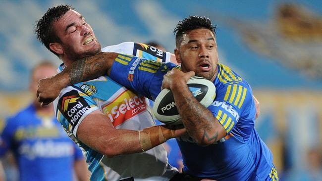 Kenny Edwards of the Eels is tackled by Luke Douglas of the Titans.