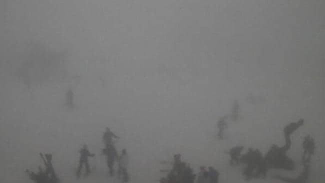 White out ... Skiers on Mt Buller's Bourke Street struggle through the wild conditions at lunchtime. Picture: Ski.com.au
