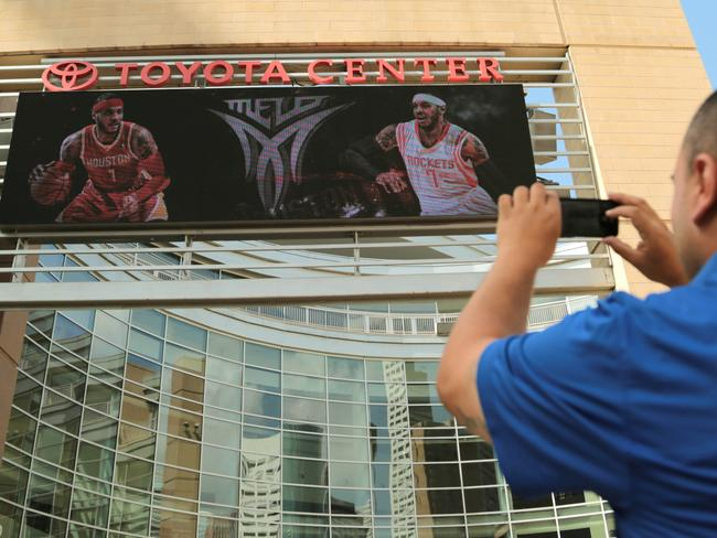 Houston Rockets fan Frank Vasquez takes a photograph of free agent forward Carmelo Anthony wearing Rockets jerseys on the Toyota Centre marquee - despite the No.7 belonging to Jeremy Lin.