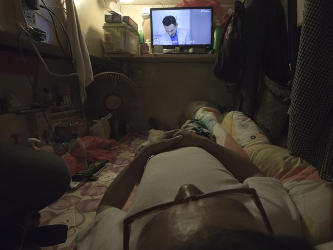 Simon Wong, an unemployed man, watches TV. Picture: Kin Cheung/AP