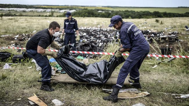 Grim scene ... Ukrainian State Emergency Service employees collect bodies of victims at the site of the MH17 crash. Photo: AFP