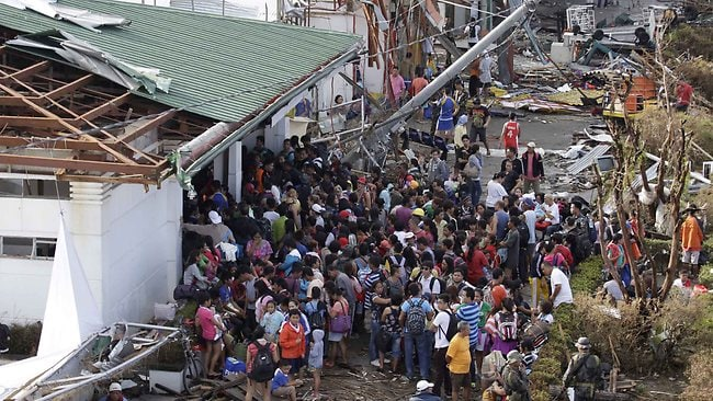 Residents queue up to receive treatment and relief supplies at Tacloban airport. Picture: Bullit Marquez