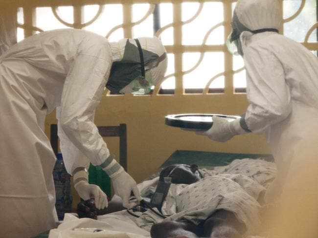 In this 2014 photo provided by the Samaritan's Purse aid organisation, Dr Kent Brantly, left, treats an Ebola patient in Monrovia, Liberia. Picture: AP / Samaritan's Purse