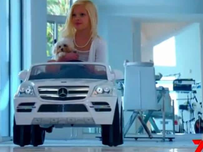 Hannaford's adopted granddaughter Bella in a white toy Mercedes with the actress's pampered pooch.