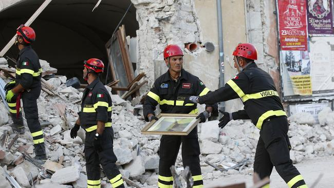 Firefighters recovering paintings from a collapsed house in central Italy where a 6.1 earthquake struck causing devastation to 293 culturally important sites. Picture: AP Photo/Antonio Calanni