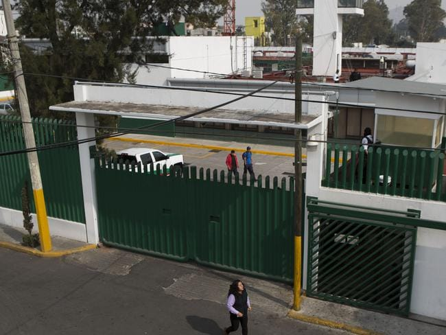 Stay ... A woman walks past the compound of the Agujas immigration detention centre, where U.S. fugitive Ethan Couth is being detained in Mexico City. Picture: AP