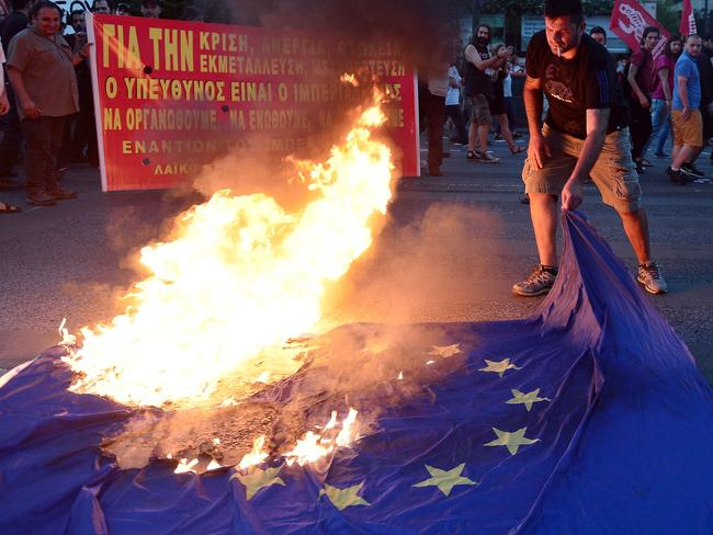An anti-EU protester burns an EU flag outside the European Commission offices in Athens. Picture: Louisa Gouliamaki