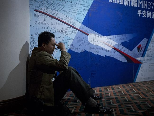 Clinging to hope ... a relative of passengers on-board Malaysia Airlines Flight 370 rests near a board covered with written wishes at a hotel in Beijing. Picture: AP