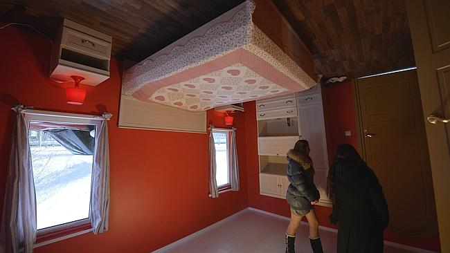 The bedroom has an upside-down bed, wardrobe and glowing lamps. Photo: AFP