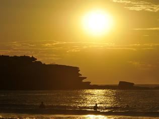 People enjoy the water at sunrise at Bondi Beach in Sydney, Wednesday, Jan. 18, 2017. Temperatures only dropped to the low-20s overnight and the weather is set to warm up to 35C in the city and 42C in the west today. (AAP Image/Joel Carrett) NO ARCHIVING
