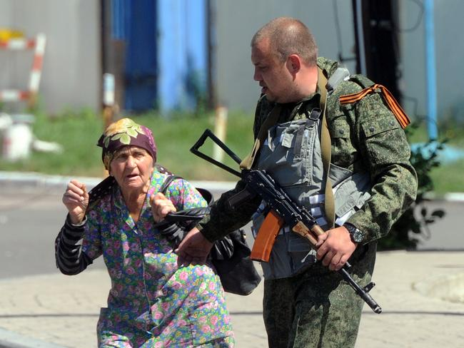 An armed pro-Russia separatist walks with a woman near the train station on July 21, 2014 as intense shelling rocked the area, in the rebel stronghold of Donetsk in eastern Ukraine. Insurgent fighters had closed off the roads in the area on the edge of the city and terrified civilians were fleeing the fighting in minibuses and on foot. Sporadic clashes have taken place around the separatist bastion as both sides have ignored calls for a ceasefire following Thursday's downing of Malaysia Airlines flight MH17 in rebel-held some 60 kilometres (40 miles) from Donetsk. Picture: AFP