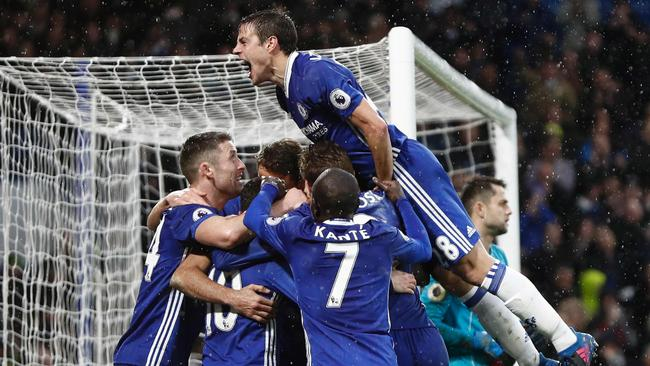 Chelsea's Spanish defender Cesar Azpilicueta (R) jumps in to join the celebration after Chelsea's Brazilian-born Spanish striker Diego Costa scored their third goal during the English Premier League football match between Chelsea and Swansea at Stamford Bridge in London on February 25, 2017. / AFP PHOTO / Adrian DENNIS / RESTRICTED TO EDITORIAL USE. No use with unauthorized audio, video, data, fixture lists, club/league logos or 'live' services. Online in-match use limited to 75 images, no video emulation. No use in betting, games or single club/league/player publications. /