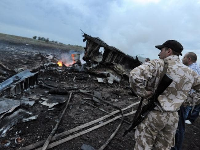 Fiery crash ... the wreckages of Flight MH17 carrying 295 people from Amsterdam to Kuala Lumpur after it was reportedly shot down in rebel-held east Ukraine. Picture: Dominique Faget