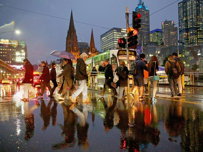 People shelter from the rain under umbrellas as they cross the road from Federation Square yesterday. Picture: Scott Barbour/Getty Images