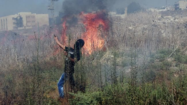 A Palestinian protester ... throws an empty tear gas canister towards Israeli troops, following a protest against the war in the Gaza strip. Picture: AP Photo/Mohammed Ballas