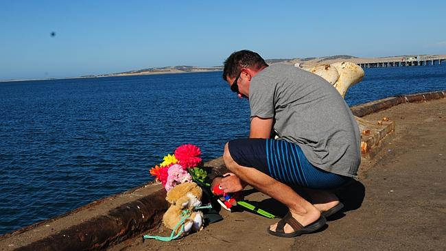 A man leaves flowers and toys at the Port Lincoln wharf in tribute. Picture: Ivon Perrin