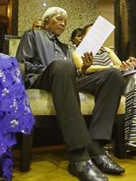"""WIRE: Former South African president Nelson Mandela reads a document in the parliament gallery in Cape Town on February 11, 2010 during a celebration for the 20th year of the icon's freedom from apartheid prison. Lawmakers cheered and sang """"Nelson Mandela, there is none like you"""" as the 91-year-old former president took his seat in the chamber, accompanied by his wife Graca Machel, smiling and waving in response. AFP PHOTO/SCHALK VAN ZUYDAM"""