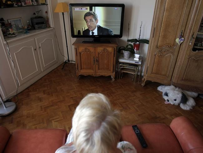 Major appearance ... a Frenchwoman watches former French President Nicolas Sarkozy in his first major TV interview since he was charged with corruption and influence peddling.