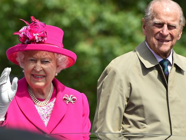 Queen Elizabeth II and Prince Philip wave to guests from their car. Picture: AFP