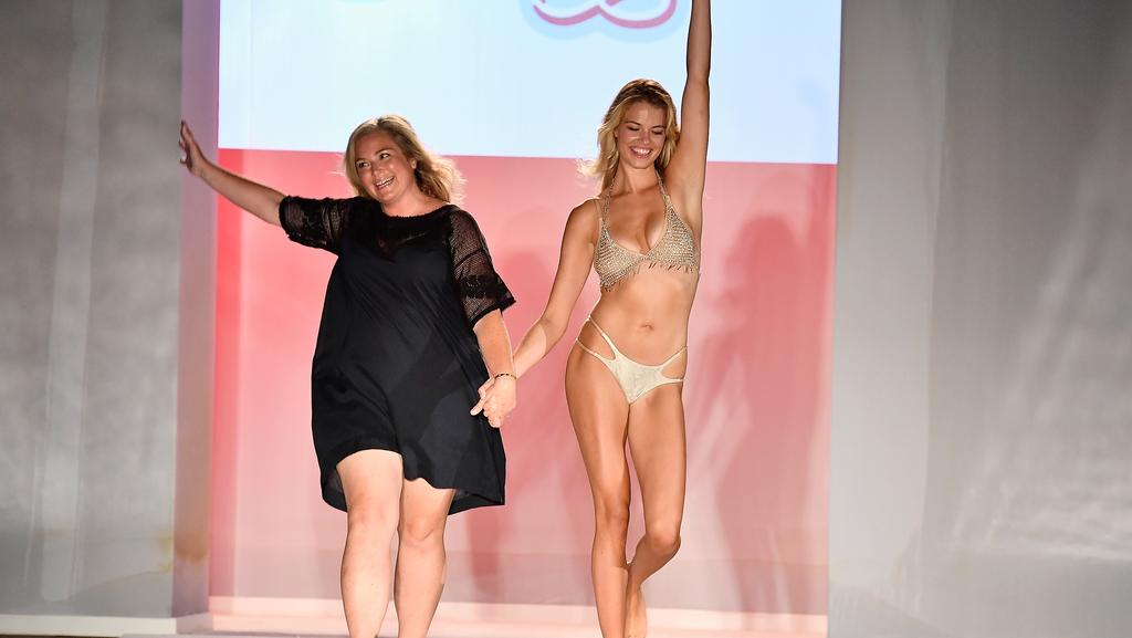 Sports Illustrated swimsuit edition editor MJ Day and a model walk the runway during SWIMMIAMI Sports Illustrated Swimsuit 2018 Collection in Florida. (Pic: Frazer Harrison/Getty)