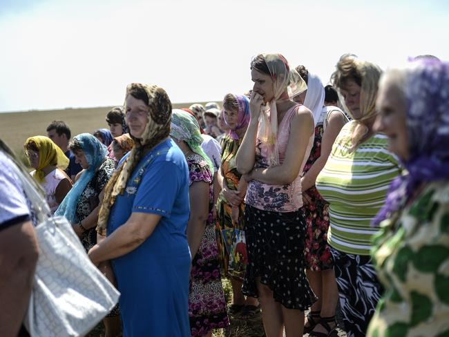 Grieving for those lost ... people attend a religious ceremony near the crash site of the Malaysia Airlines Flight MH17 near the village of Hrabove (Grabovo). Picture: AFP