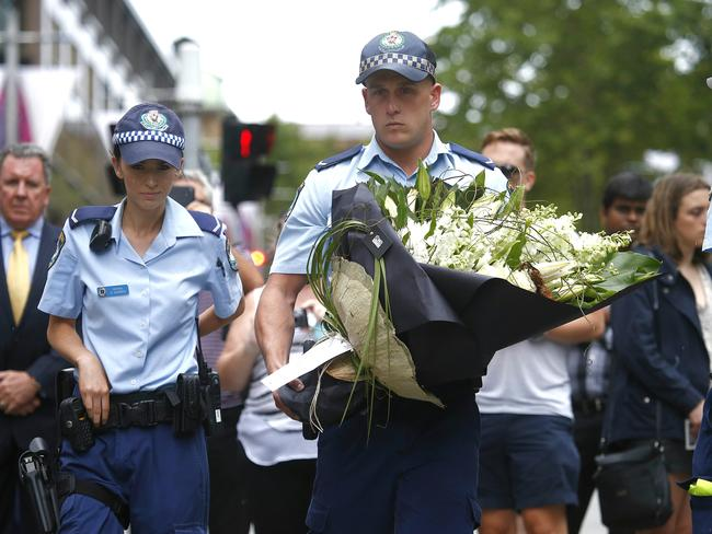 Police officers visit the flower memorial. Picture: Bradley Hunter