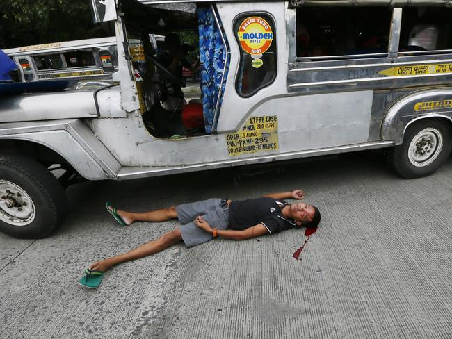 A bloodied protester lies next to a passenger vehicle after he was injured in a violent dispersal outside the US Embassy in Manila. Picture: Bullit Marquez.