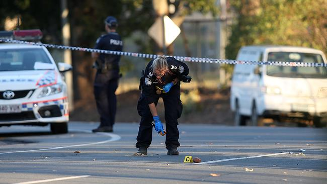 A police officer marks out the crime scene at Woodridge. Picture: Marc Robertson/AAP.