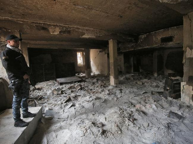 A member of the Iraqi government forces inspects the damage inside the destroyed museum of Mosul. Picture: Ahmad Al-Rubaye