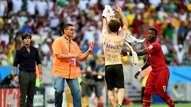 A pitch invader is approached by Sulley Muntari.
