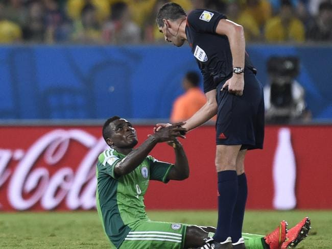 New Zealand referee Peter O'Leary helps Nigeria forward Emmanuel Emenike stand up during the group F World Cup match against Bosnia-Herzegovina.
