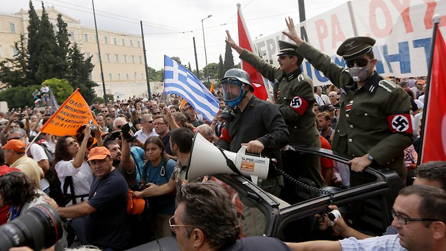 "Two men dressed as German World War II soldiers with Nazi swastika armbands sit in the back of an open vehicle, in front of a banner reading ""Merkel out, undesirable"" during a protest in Athens on Tuesday Oct. 9, 2012. German Chancellor Angela Merkel makes her first visit to Greece since the eurozone crisis began here three years ago. Her five-hour stop is seen by the government as a historic boost for the country's future in Europe's shared currency, but by protesters as a harbinger of more austerity and hardship. More than 7,000 police will be on hand, cordoning off parks and other sections of central Athens, to keep demonstrators away from the German leader who is due to arrive today in the Greek capital for talks with conservative Prime Minister Antonis Samaras. . (AP Photo/Lefteris Pitarakis)"