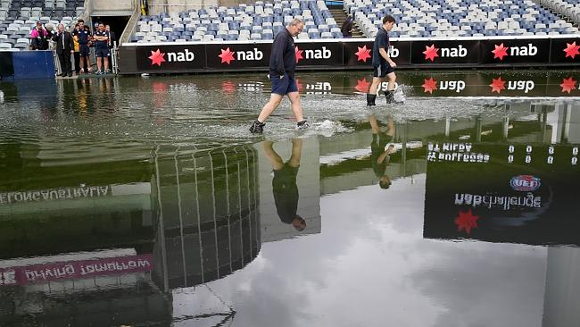 Geelong staff inspect the Simonds Stadium playing surface. Picture: Wayne Ludbey,