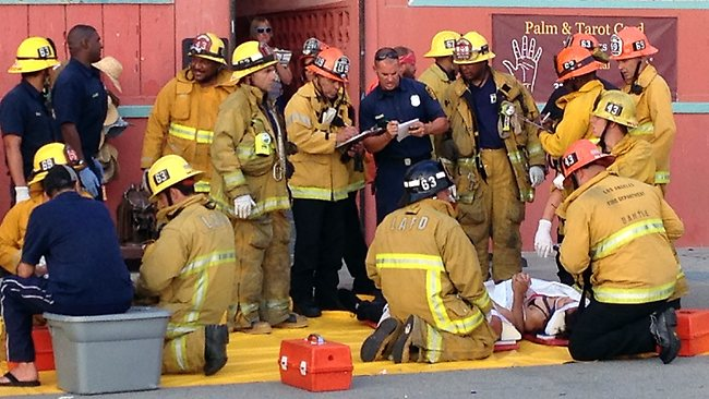Police and fire officials assist an injured pedestrian at the scene where a car drove through a packed afternoon crowd along the Venice Beach boardwalk in Los Angeles, Saturday, Aug. 3, 2013. At least a dozen people were injured, two of them critically, according to police. (AP Photo/Venice311.org, Alex Thompson)