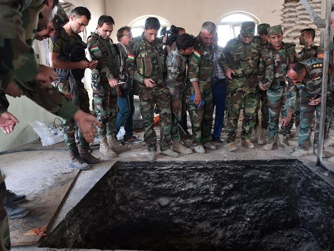 Kurdish Peshmerga soldiers stand around a tunnel dug by IS in a recently recaptured house in Bartella, near Mosul in Iraq. Picture: Carl Court.