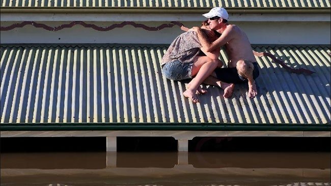 Man and his daughter on the roof of their Bundaberg home