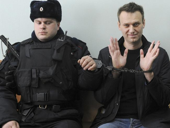 Russian opposition leader Alexei Navalny, right, poses for press in court in Moscow, Russia. Picture: AP
