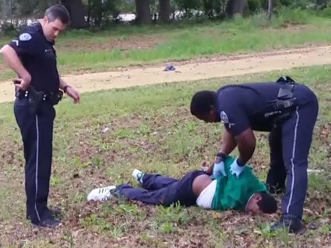 Police officer Michael Slager (L), 33, looking on as another police officer checks Walter Scott (on ground), 50, in the city of North Charleston on April 4, 2015.