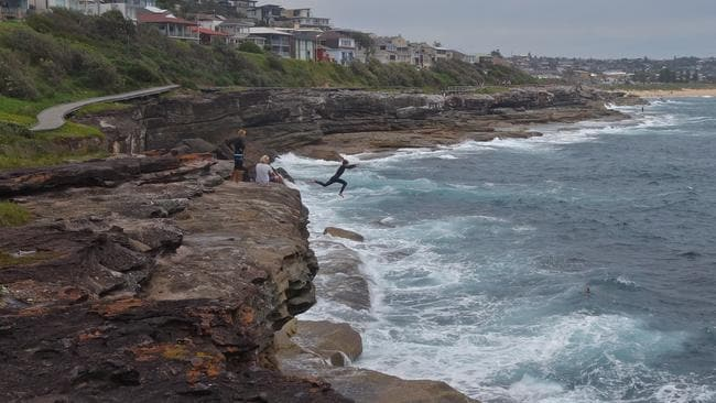 Young teenagers take a death-defying leap from the rocks at Curl Curl. Picture: Edita Pahor.