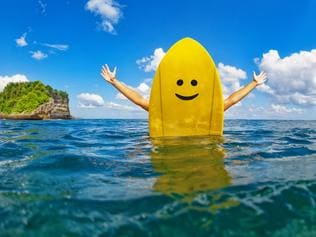 Young happy surfer girl sit on yellow surf board with smiley face and have fun. Healthy lifestyle, people water sport lessons, swimming activity in summer surf camp on family beach vacation with children