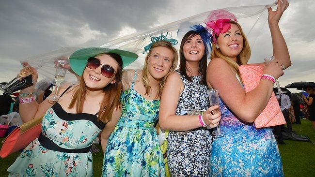 Hannah, Jessica, Niamh, and Susan, all from Ireland, try to keep dry at the Melbourne Cup. Picture: Alex Coppel