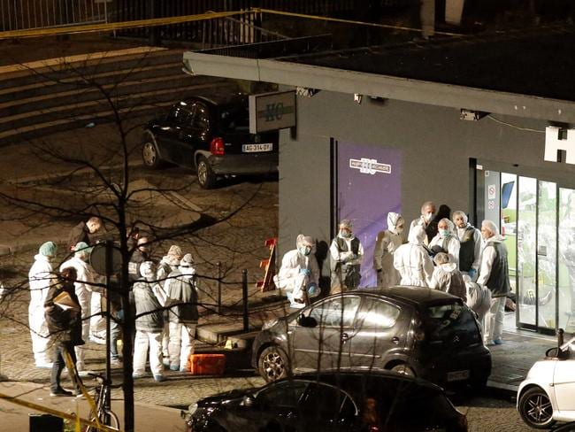 Investigations underway ... Forensic officers gather outside the kosher grocery store. Picture: AP/Francois Mori