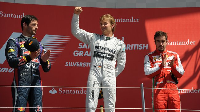Mark Webber (L) applauds Nico Rosberg (C) after the German's British Grand Prix victory.
