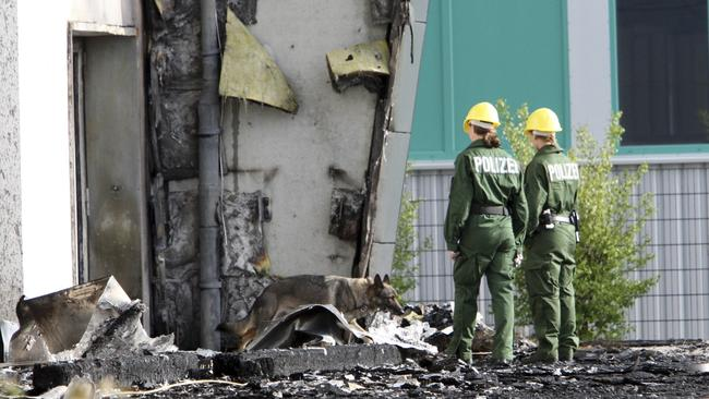 Police officers and their sniffer dog examine the ruins of a burned out gym in Nauen, Germany. A German court has convicted a far-right politician for burning down the building intended as housing for refugees. Picture: AP