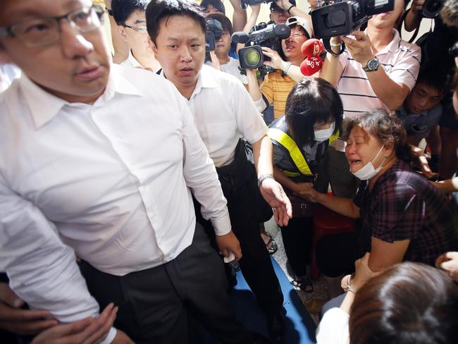 Grief-stricken ... TransAsia chairman Vincent Lin, left, leaves after meeting a family member, right, of a victim in the doomed plane.