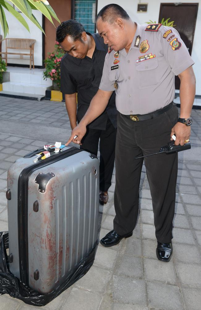 Crime scene ... a policeman looking at a suitcase where the body of a woman was found inside, displayed at a police station in Nusa Dua on the Indonesian resort island of Bali. Picture: AFP