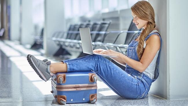 Shot of a young woman using a laptop while sitting on the floor in an airport