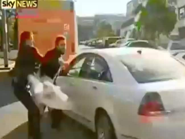 No fear ... a protester lunges at a car carrying Julie Bishop as she leaves the C20 summit in Melbourne. Picture: Sky News