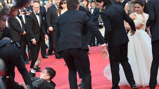 Vitalii Sediuk is dragged away by minders after he tried to slip under the voluminous gown of US actress America Ferrera (right) on the red carpet of the Cannes Film Festival.